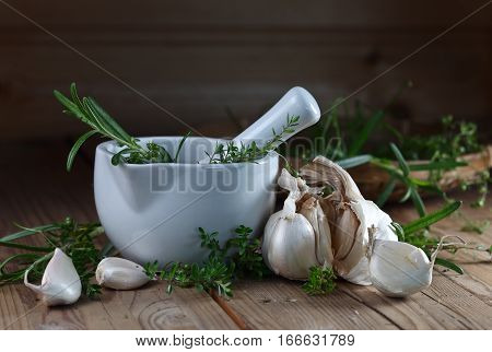 Garlic With Rosemary And Thyme On A Old Wooden Table