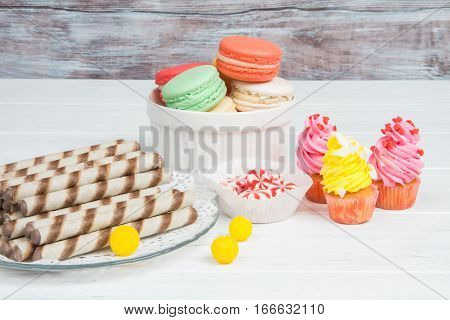 Candy Bar: Macaroons, Cupcakes And Candy On Wooden Background.