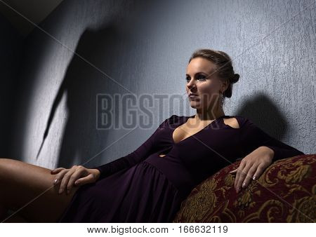 Young Woman In Evening Dress And The Culprit's Shadow On The Wall