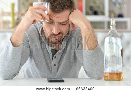 young man drinking alcohol, in bad mood