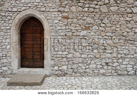 Wooden backdoor with pointed arch (gothic). The door is located in a wall with white irregularly shaped stone blocks which belongs to an ancient fortress or old castle. It is made of riveted wood planks and is locked and closed.