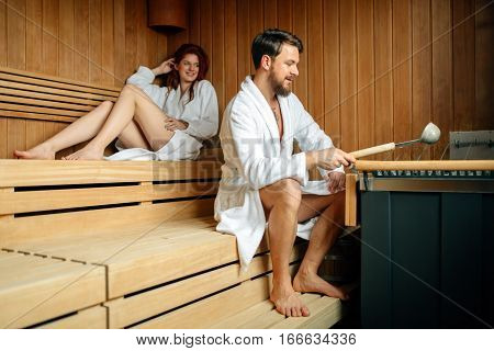 Couple resting and sweating in a modern sauna