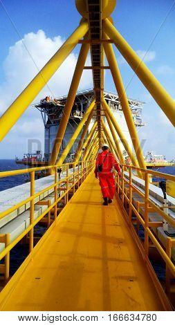 Operator on oil and gas platform walking on bridge to living quarter platform.