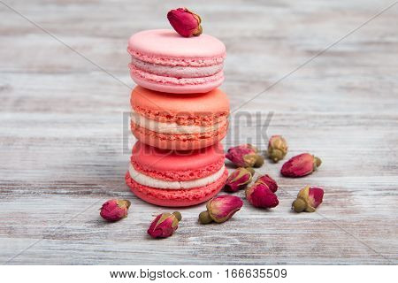 Pink Macaroons And Rosebuds On Wooden Table. Valentine's Day