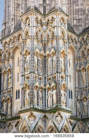 Wells United Kingdom - August 6 2016: Sculpted figures gallery of royalty fills the niches of the north west buttress of Wells cathedral.