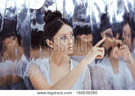 Portrait of futuristic young woman touching reflection in mirror. Reflection of our mind and soul concept. Beautiful young multi-racial asian caucasian model cyber girl in silver urban clothes with conceptual hairstyle and make-up in metallik silver capsu