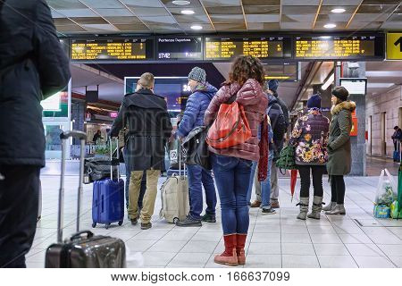 Naples Italy - January 17 2017: Some passengers with luggage waiting for the arrival of the train watching the board of arrivals / departures in the train station.
