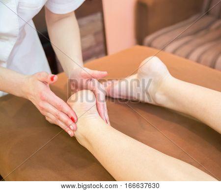 Relaxing revitalizing foot massage. Work masseur at spa salon.