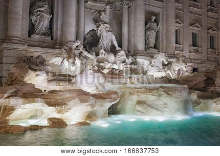 The famous Trevi fountain shooting night in its central part with the main niche. The long exposure shows the movement of the falls. Trevi fountain is taken laterally echoing the large tub with water artificially illuminated.