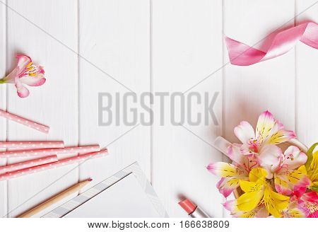 Flowers, paper straws, pink ribbon and other cute objects on the white wooden table, top view