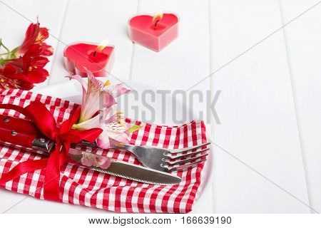 Valentine's day table setting. Fork, knife with red ribbon and little flowers on the plate with red and white checkered serviette.