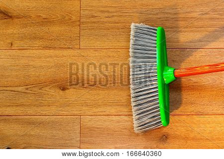 cleaning brown wooden floor with a broom