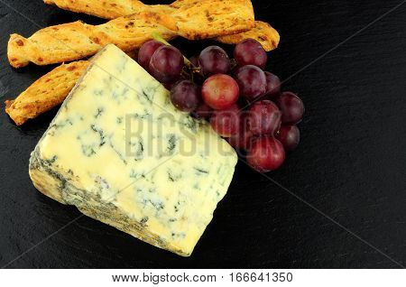 Blue veined strong English Stilton cheese wedge and red grapes on a stone slate background