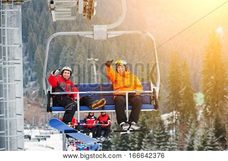 Skier and snowboarder riding up to the top of the mountain on ski lift and showing thumbs up gestures of good class with an beautiful view nature. Bukovel Ukraine