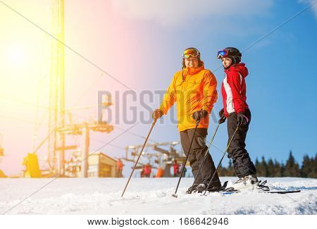 Couple Holding Skis Standing Together At A Winter Resort