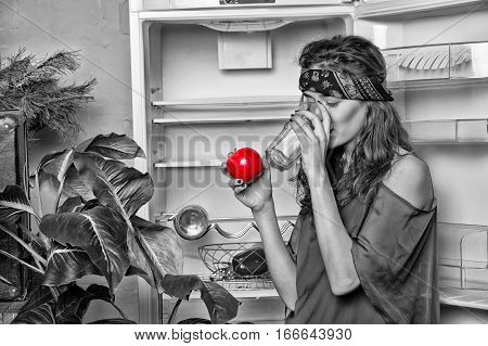 pretty girl or sexy woman hippie with cute face in handkerchief or bandana on curly hair near fridge plant drink from glass and holds red apple black and white