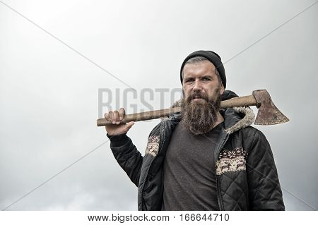 Bearded Handsome Serious Man With Rusty Axe Against Cloudy Sky