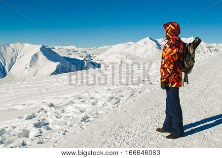 Photo of the Tourist with backpack enjoy view on top Caucasus Mountain Range. Inspiring Landscape. Blue sky and white snow. Sport hike in holidays. Negative space for text.