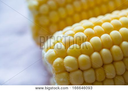 Fresh sweet corn on pink napkin. Two corn cobs.