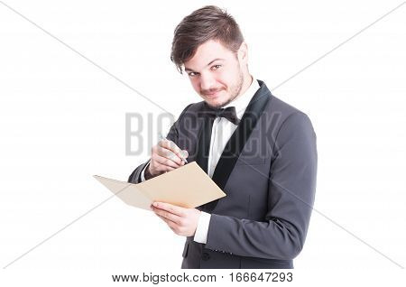 Handsome Man Wearing Tuxedo And Bowtie Writing On Notebook