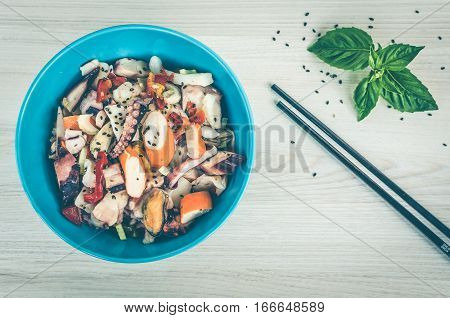 Fresh salad with seafood tomatoes and celery in yummy asian style with basil on wooden background. Asian salad with squid octopus shrimp mussel and black sesame seeds. Asian food. Seafood concept. Top view.