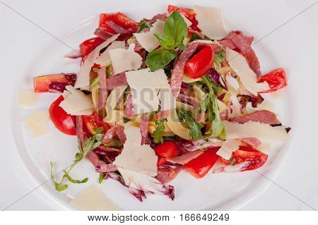 fettuccine with fresh vegetables and bacon on white plate