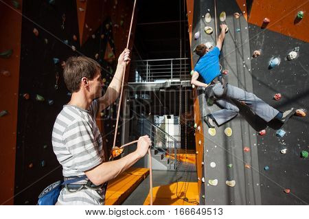 Belayer Insuring The Climber On Rock Wall Indoors