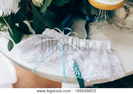 Wedding accessories: Bride's garter with turquoise bow and delicate wedding bow with white and cyan ribbons. Closeup