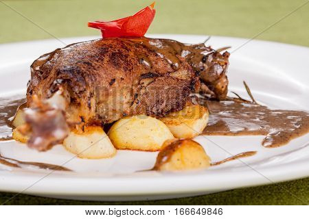 roasted piece of meat with sauce with baked potatoes