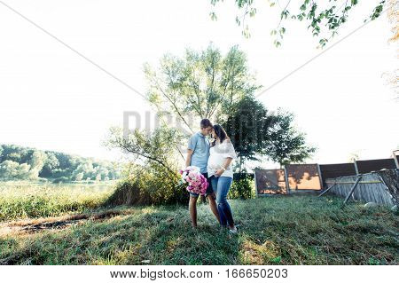 Modish Expecting Couple Stands In Warm Embraces Under Green Tree