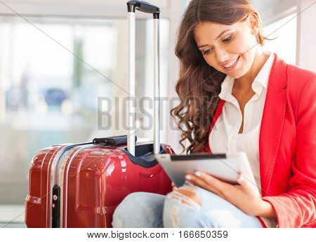 Airport woman on smart phone at gate waiting in terminal. Air travel concept with young casual business woman sitting with carry-on hand luggage trolley. Beautiful young mixed race female professional