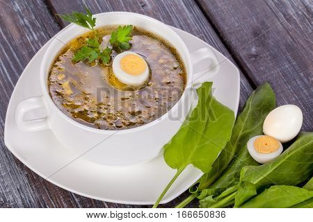 Green soup with sorrel and egg in a deep plate