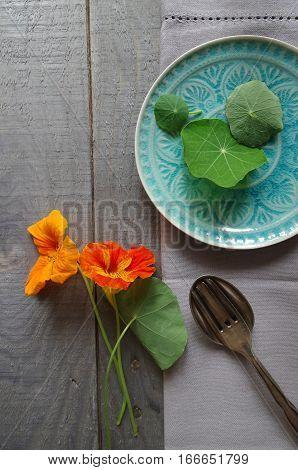 edible flowers nasturtium with blue plate - topview