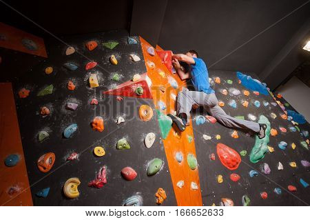Strong rock climber practicing artificial rock climbing on a rock wall indoors without special equipment