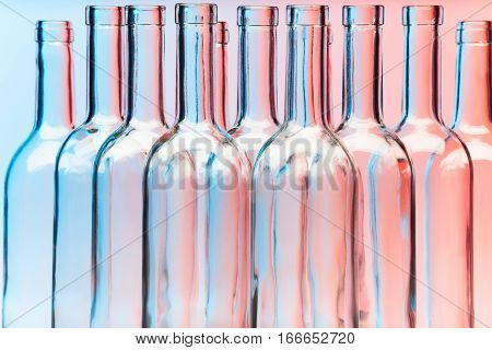 Close-up picture of several clear glass wine bottles