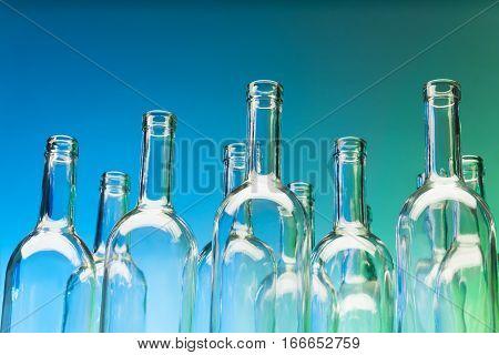 Crystal bottlenecks of empty glass wine bottles on blue background