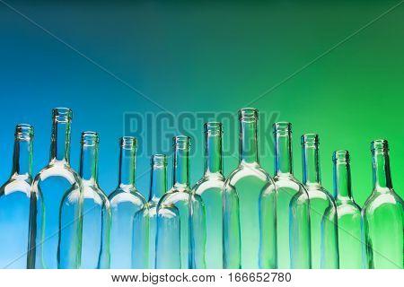 A dozen crystal bottlenecks of empty glass wine bottles standing in line