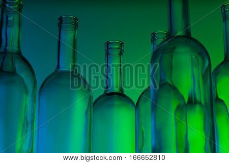 A group of clear glass wine bottles standing in green light