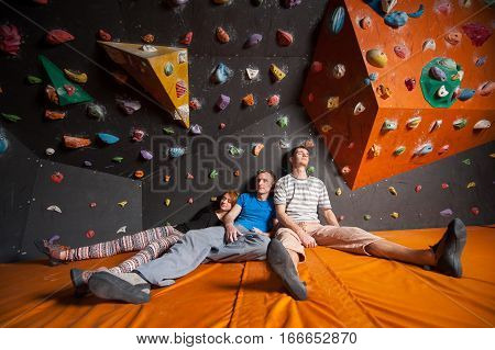 Three Tired Climbers On The Mat Near Rock Wall Indoors