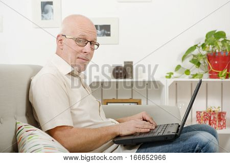 Portrait of a handsome mature man using laptop on sofa