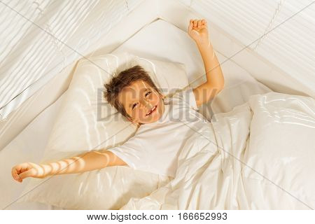 Top view portrait of happy kid boy waking up in his white bedroom in the morning