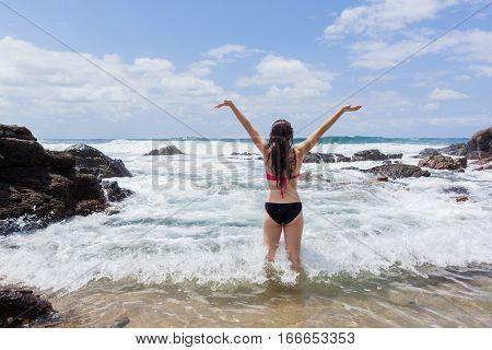 Girl teenager summer celebration swimming beach ocean waves rock tidal pool