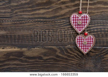 Dark Wood Background And Two Checkered Heart Hanging On Rope