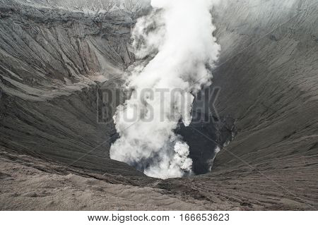 Huge volcano crater erupting ashes and smoke