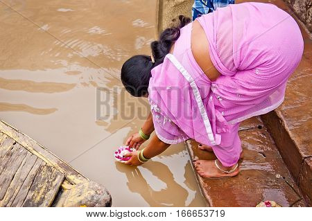 Woman pilgrim leaving a flower offer in the Ganges Varanasi