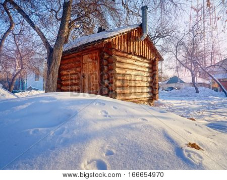 A photo of a beautiful wooden outhouse with a roof under the snow