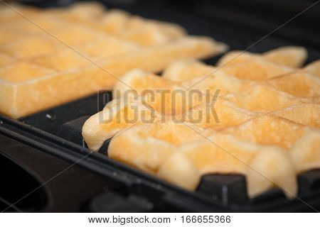 homemade waffles are cooked in the waffle iron. close up