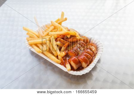 Closeup to Currywurst serving with fries and spicy sauce a traditional german dish.