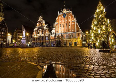 RIGA LATVIA - 1ST JAN 2017: The outside of the House of Blackheads at night during the Christmas period. People can be seen.