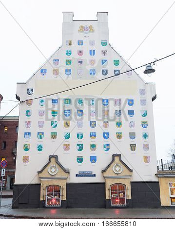 RIGA LATVIA - 2ND JAN 2017: The outside of buildings in Riga Old Town during the day showing a building with lots of Shield Emblems on.